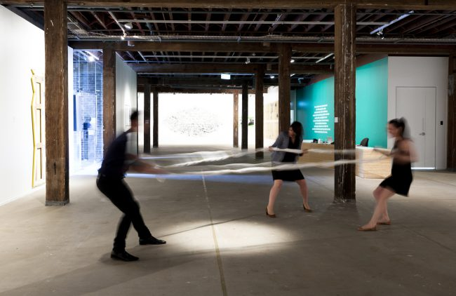 Three people pull a circle of rope in different directions, in an empty room with pillars.