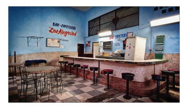 Colour photo of empty bar with blue walls and checked tiled floor.