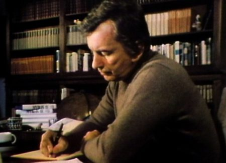 Gore Vidal in his 30s writing at a desk.