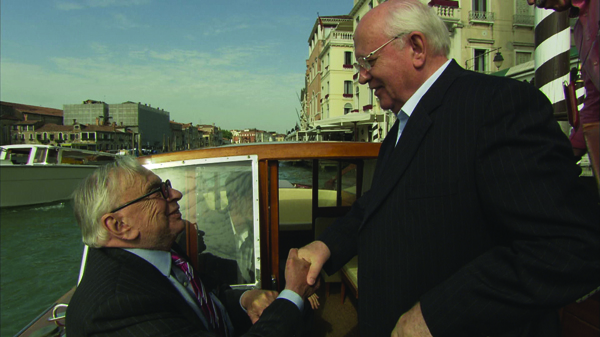 Gore Vidal on a canal boat shakes hand with another man.