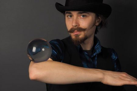 Young white man with beard and hat balancing crystal ball on his elbow.