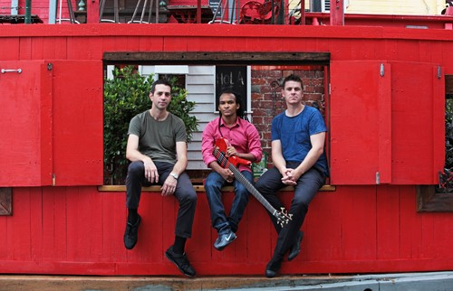 3 young men, 2 white, 1 black sitting in bright red window.