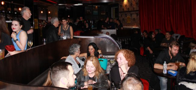 Nightclub interior with diverse, smiling crowd seated at tables.