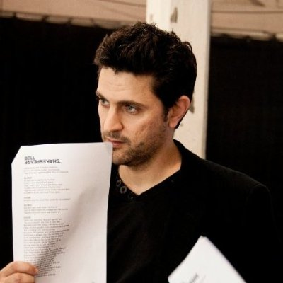 Young, bearded white man holding up script.