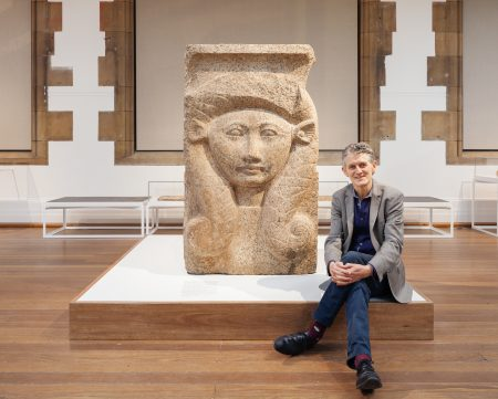 Michael Turner, Snr Curator of the Nicholson Museum, University of Sydney, with a carved granite capital depicting the goddess Hathor