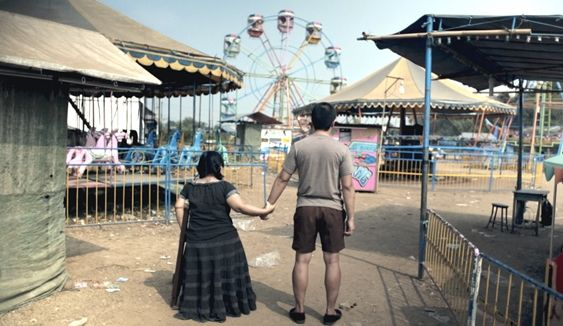 Man and woman from behind, holding hands, looking at deserted fairground.