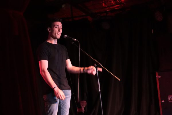 A young man in a black shirt and blue jeans speaking on stage.