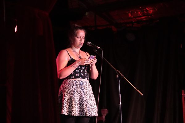 Young woman reading from script in front of a microphone on stage.