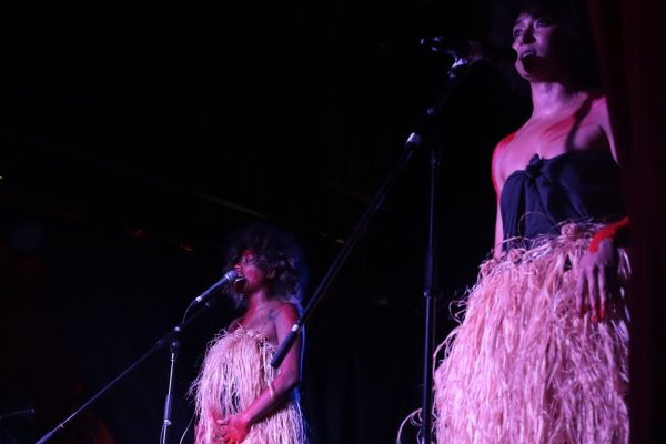 Two women on stage with grass skirts and red paint on them.