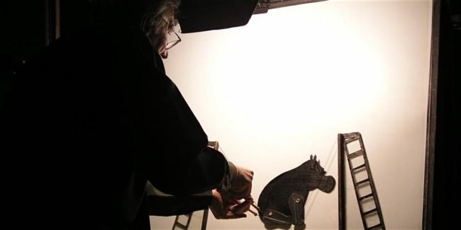 Richard Bradshaw adjusted a puppet of a hippo with a backlight