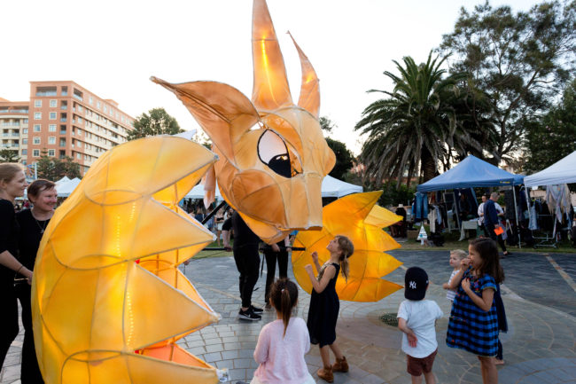 Large mystical animal puppet on the street with children underneath
