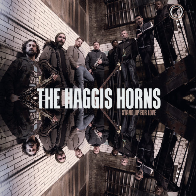 Album art for The Haggis Horns'album, Stand Up for Love. A photo of the band members and their instuments standing in a stairway.